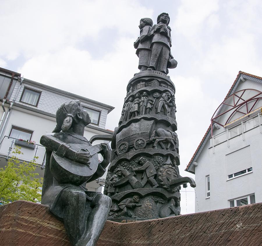 Brunnen mit Mandoline spielender Mädchen-Figur - Station eines Audio Guide