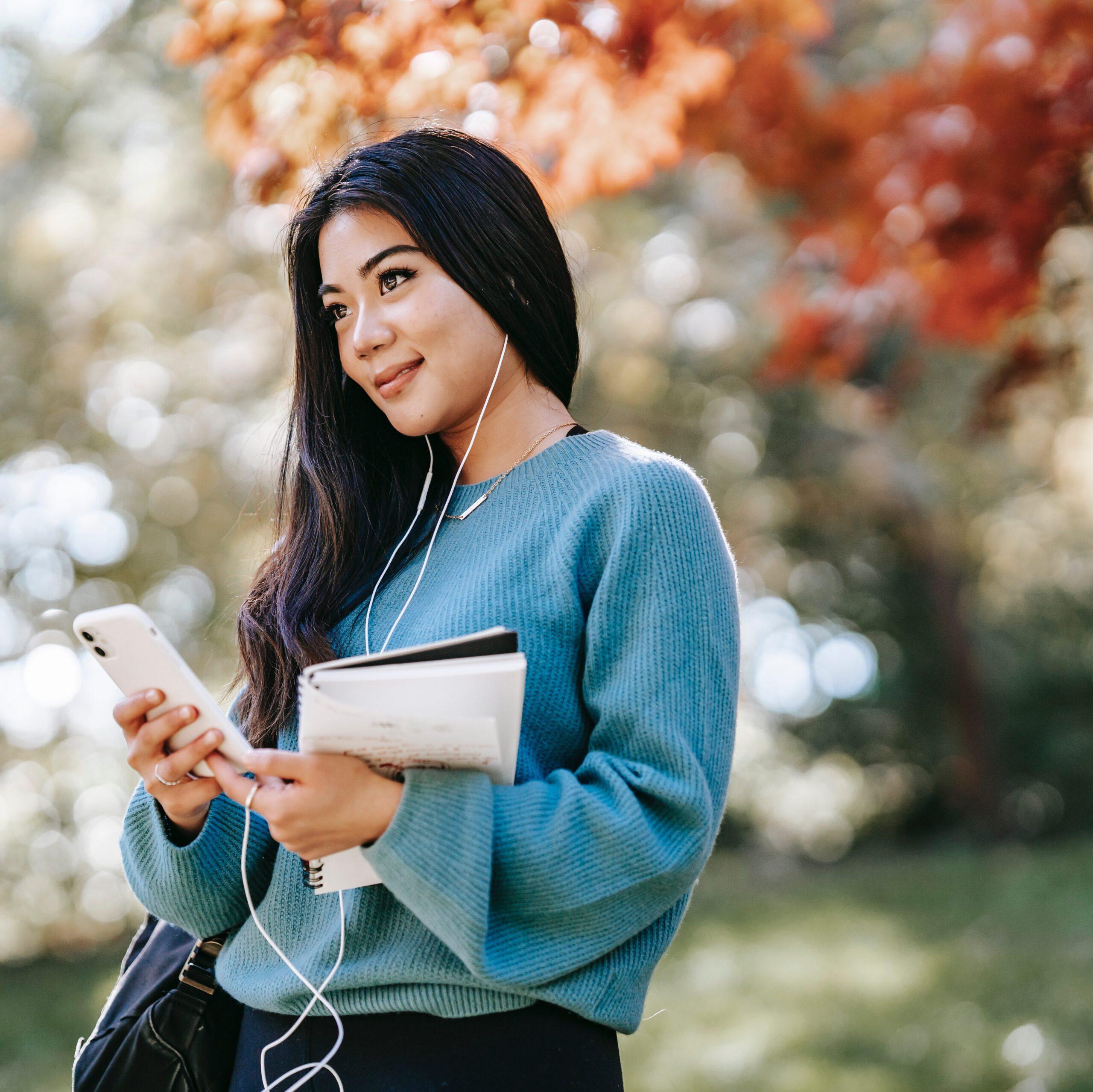 Frau mit Smartphone in der Hand und Kopfhörern in den Ohren hört den Audio Guide